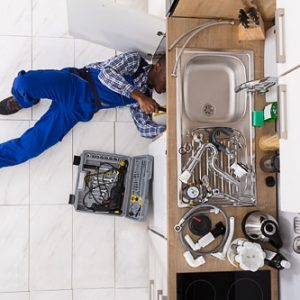 High Angle View Of Handyman Lying On Floor Repairing a commercial Sink In Kitchen With Toolbox